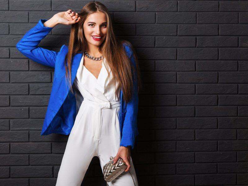Fashionable studio image of   stylish attractive young woman in casual white costume and blue jacket holding luxury purse posing on black urban brick wall background.